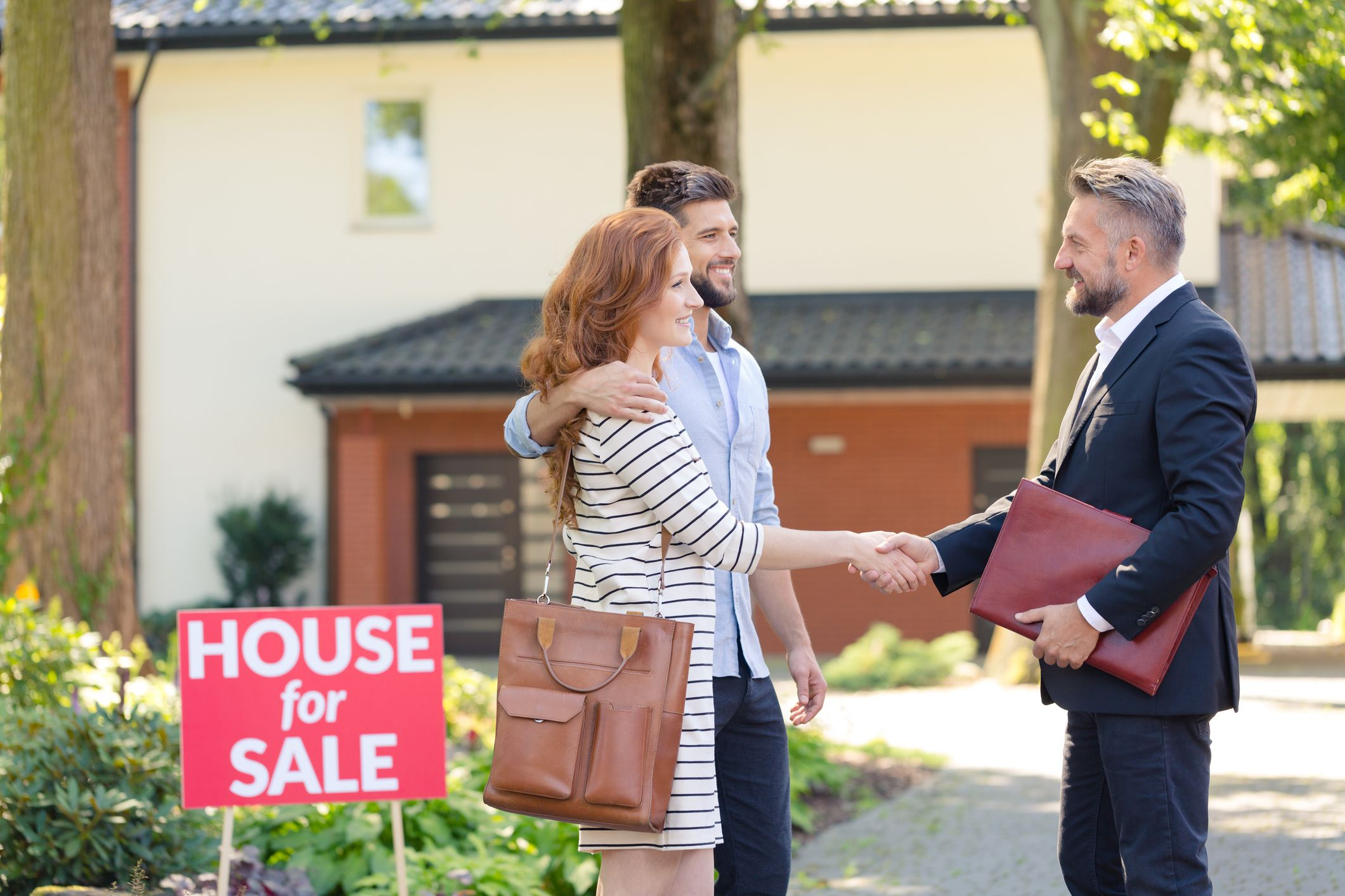 Seller congratulating a young couple buying house in suburbs